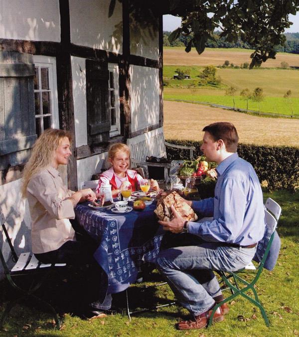 Auch eine Ferienwohnung kann ein Qualitätsgastgeber sein. Eine Familie frühstück gemütlich draußen.