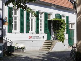 Außenansicht auf das Otto Modersohn Museum in Tecklenburg, Weißes Steinhaus Sprossenfenstern und grünen Fensterläden und grüner Eingangstür A
